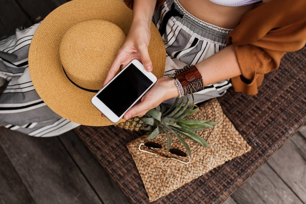 Close de mãos femininas segurando um telefone celular