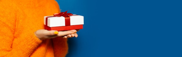 Close de mãos femininas segurando uma caixa de presente branca com laço vermelho