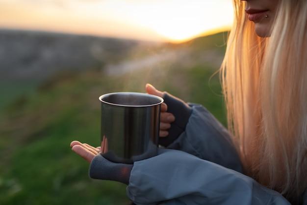 Close de mãos femininas segurando uma caneca de aço com chá quente ao ar livre
