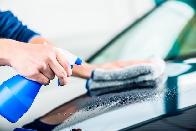 Close de mãos masculinas limpando carro com spray de limpeza e toalha de microfibra ao ar livre no lava-rápido
