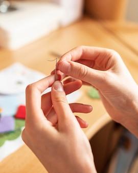 Close de mãos segurando agulha e linha