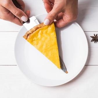 Close de mãos segurando uma fatia de torta