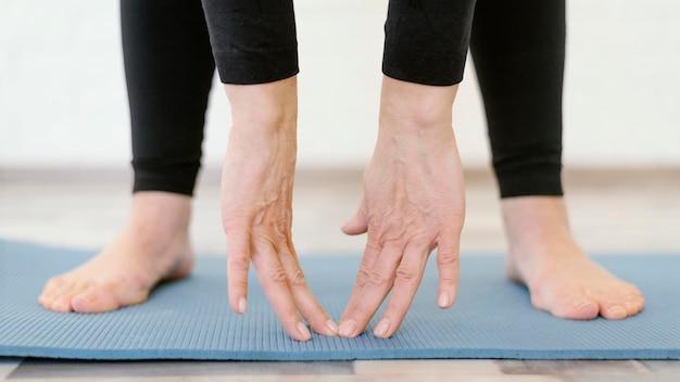 Close de mãos tocando o tapete de ioga