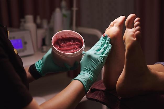 Close de massageando o pé com esfoliação durante uma pedicure profissional em salão de beleza