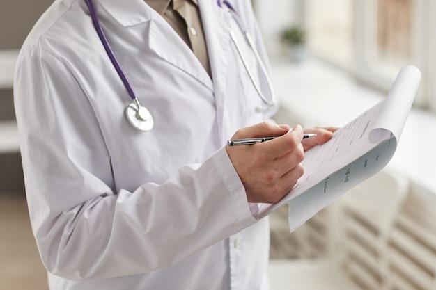Close de médico de jaleco branco preenchendo ficha médica com caneta no hospital