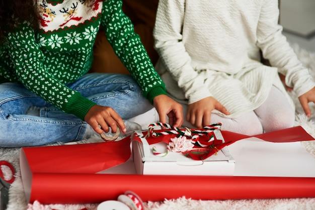 Close de meninas embalando presentes para o natal
