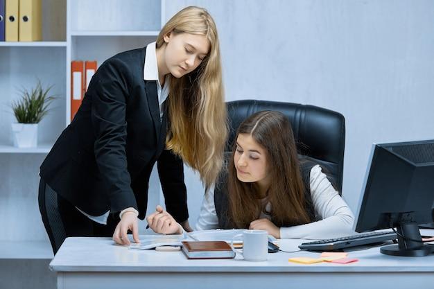 Close de meninas trabalhando juntas em um projeto comum no escritório