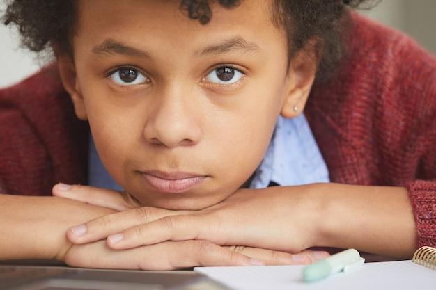 Close de menino africano olhando deitado na mesa cansado de estudar