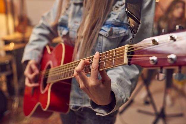Close de mulher aprendendo a tocar guitarra elétrica durante a aula de música no estúdio