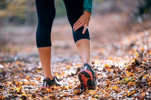 Close de mulher desportiva com lesão muscular e segurando a perna dolorida na floresta.