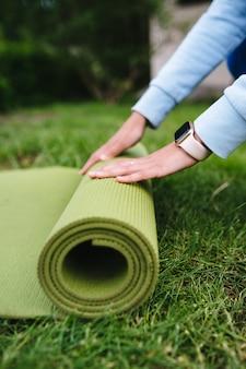 Close de mulher dobrando roll fitness após malhar no parque