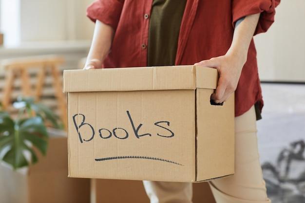 Close de mulher embalando os livros na caixa durante a realocação