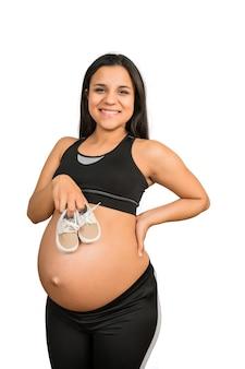 Close de mulher grávida segurando sapatos de bebê na barriga