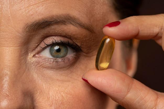 Close de mulher idosa segurando comprimido de óleo