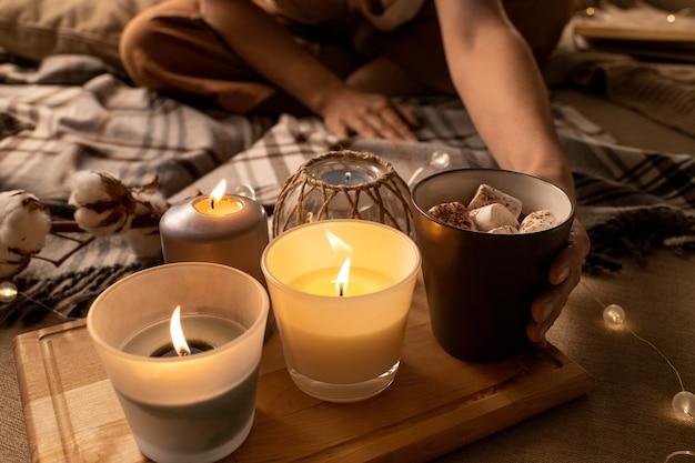 Close de mulher tomando chocolate com marshmallow na bandeja com velas acesas