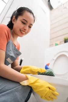 Close de mulheres asiáticas usando luvas limpando o banheiro com uma esponja no banheiro