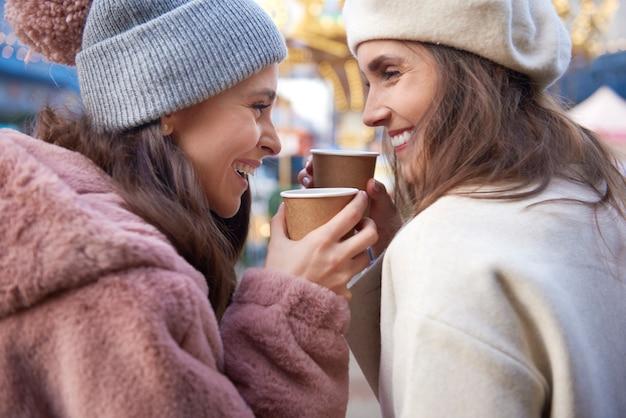 Close de mulheres bebendo vinho quente ao ar livre