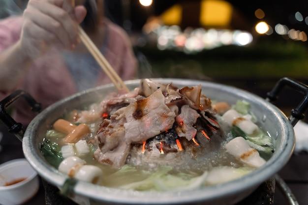 Close de mulheres comendo carne de porco para churrasco no fundo do bokeh