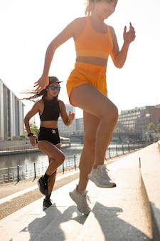 Close de mulheres correndo em escadas