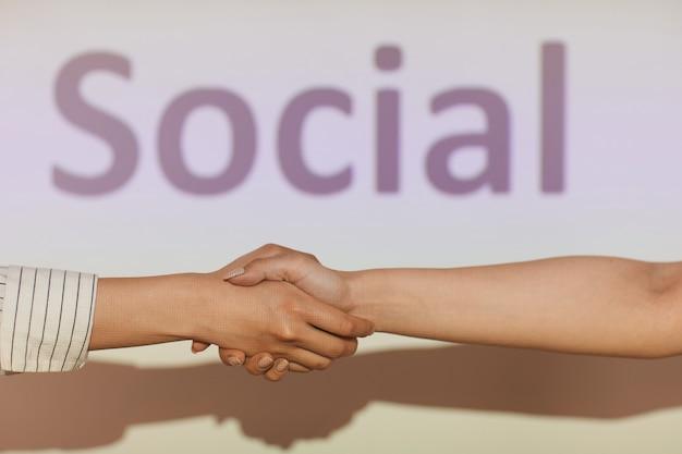 Close de mulheres irreconhecíveis fazendo aperto de mão na tela de projeção com inscrição social