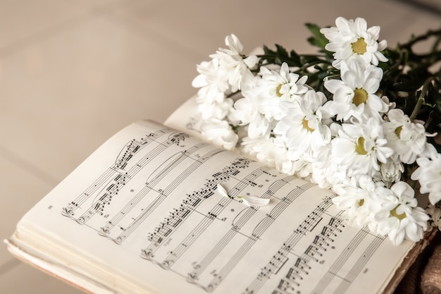 Close de notas musicais e um buquê de flores