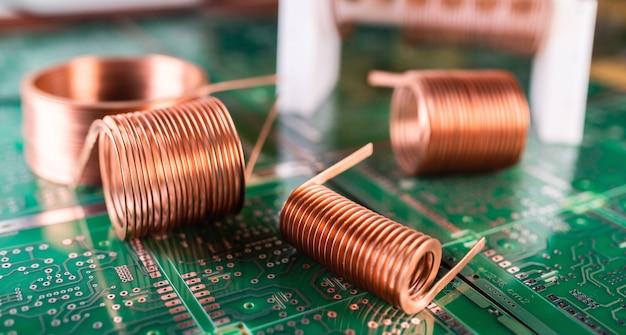 Close de novelos de fio de cobre trançado sobre um microcircuito verde