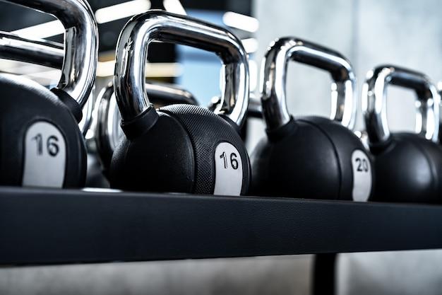 Close de novos halteres em um rack em uma academia