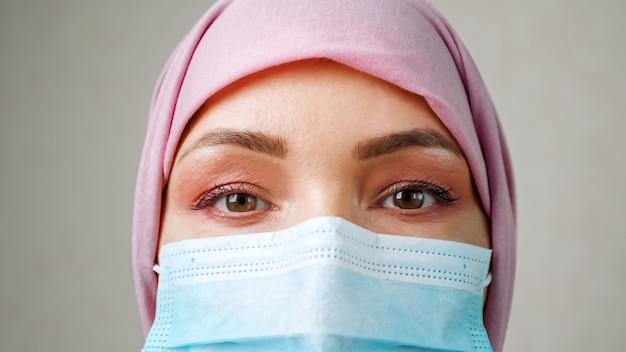Close de olhos de mulher muçulmana usando máscara médica