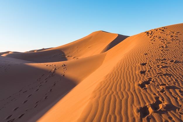 Close de ondulações de areia e trilhas em dunas de areia em um deserto contra um céu azul claro