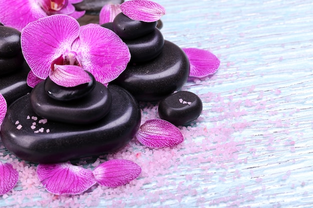 Close de orquídea violeta e pedras zen Foto Premium