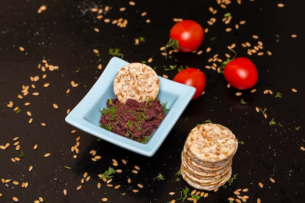 Close de pasta de azeitona em uma tigela sobre a mesa com biscoitos e tomates sob as luzes