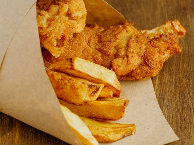 Close de peixe com batatas fritas em filme de papel
