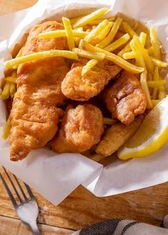 Close de peixe e batatas fritas com rodela de limão
