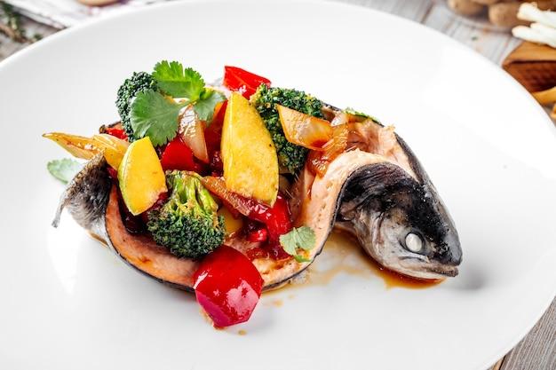 Close de peixe gourmet robalo cheio de vegetais em um prato branco
