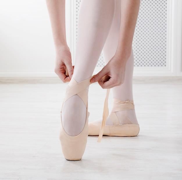 Close de pernas de bailarina calçando sapatilhas de balé