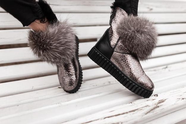 Close de pernas femininas em tênis elegantes prateados com pelo cinza