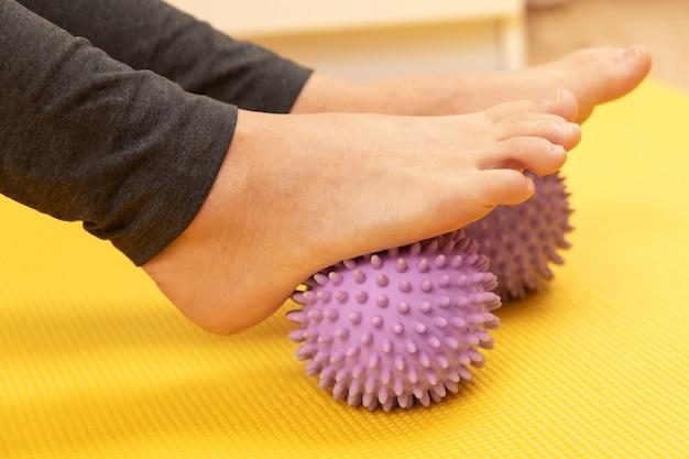 Close de pés femininos e bolas de massagem espinhosas