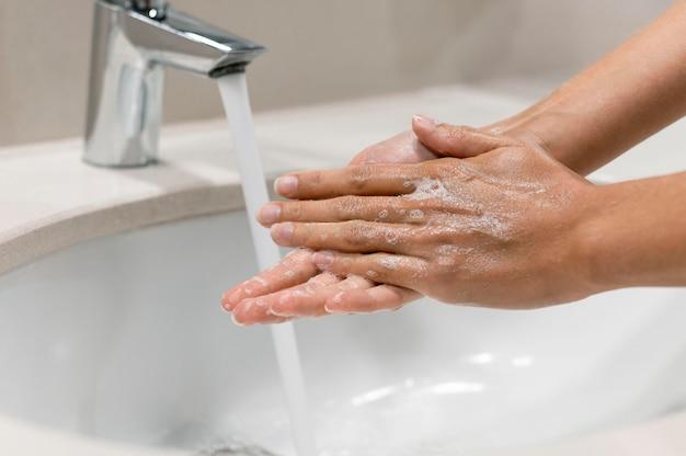 Close de pessoa lavando as mãos