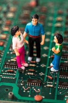 Close de pessoas de brinquedo na placa de circuito eletrônico verde