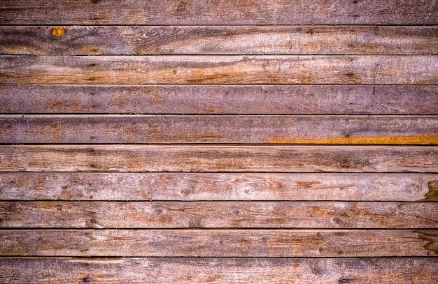 Close de pranchas de madeira envelhecidas em marrom escuro