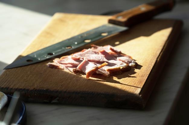 Close de presunto fatiado para sanduíches em uma tábua de cortar