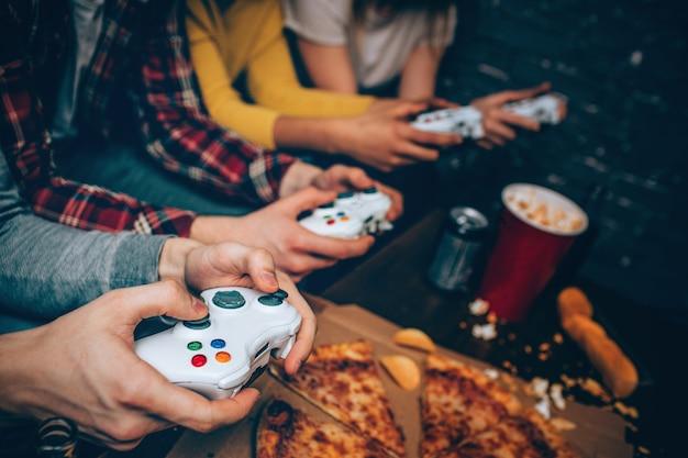 Close de quatro consoles de jogos para as pessoas colocarem em suas mãos