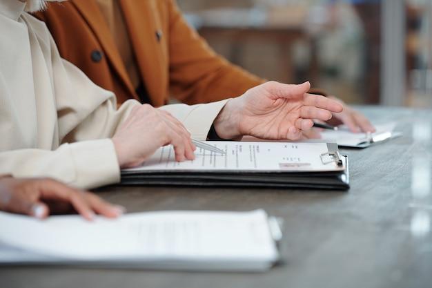 Close de recrutadores irreconhecíveis sentados em fila e lendo o currículo enquanto fazem perguntas ao candidato na entrevista de emprego