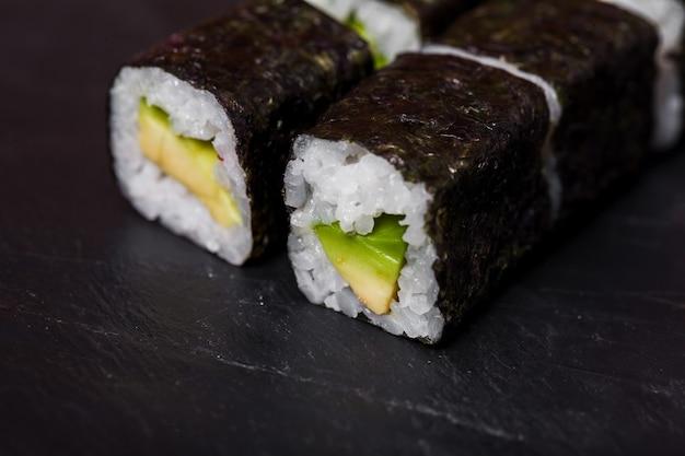 Close de rolinhos de sushi com abacate em um fundo de ardósia preta