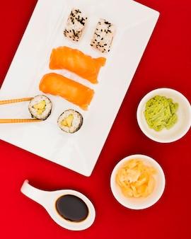 Close de rolos de sushi e sashimi servidos com wasabi; calda de gengibre e molho de soja