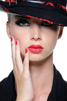 Close de rosto de mulher bonita com lábios vermelhos brilhantes e unhas no chapéu da moda