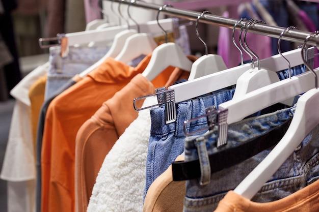 Close de roupas femininas casuais coloridas penduradas em cabides de madeira brancos
