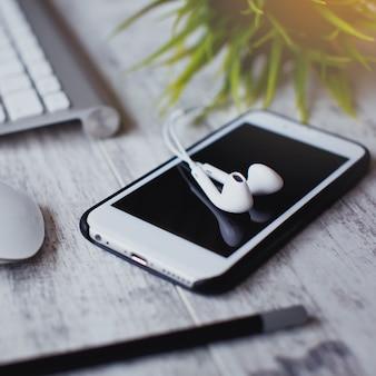 Close de smartphone e fone de ouvido na mesa de madeira
