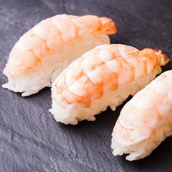 Close de sushi ebi com camarão em fundo de ardósia preta
