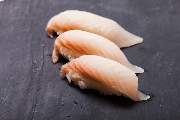 Close de sushi tai nigiri em fundo de ardósia preta
